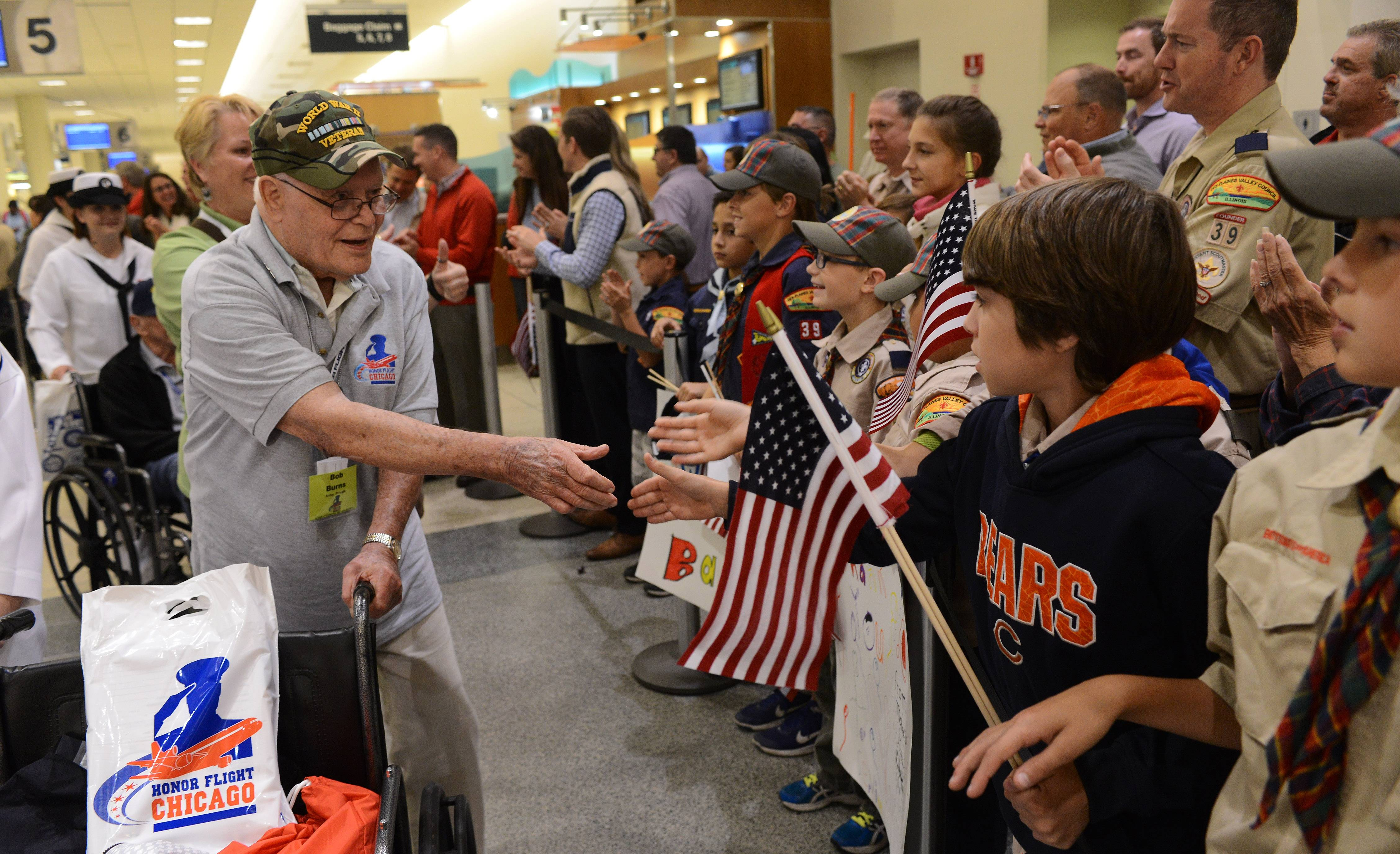 About 2,000 people stage a welcome home rally for Bob Burns of Ingleside as he and 84 other World War II veterans arrive at Chicago Midway International Airport. The veterans were guests of Honor Flight Chicago, which flew what could be its last full group of World War II veterans to Washington, D.C., last week.