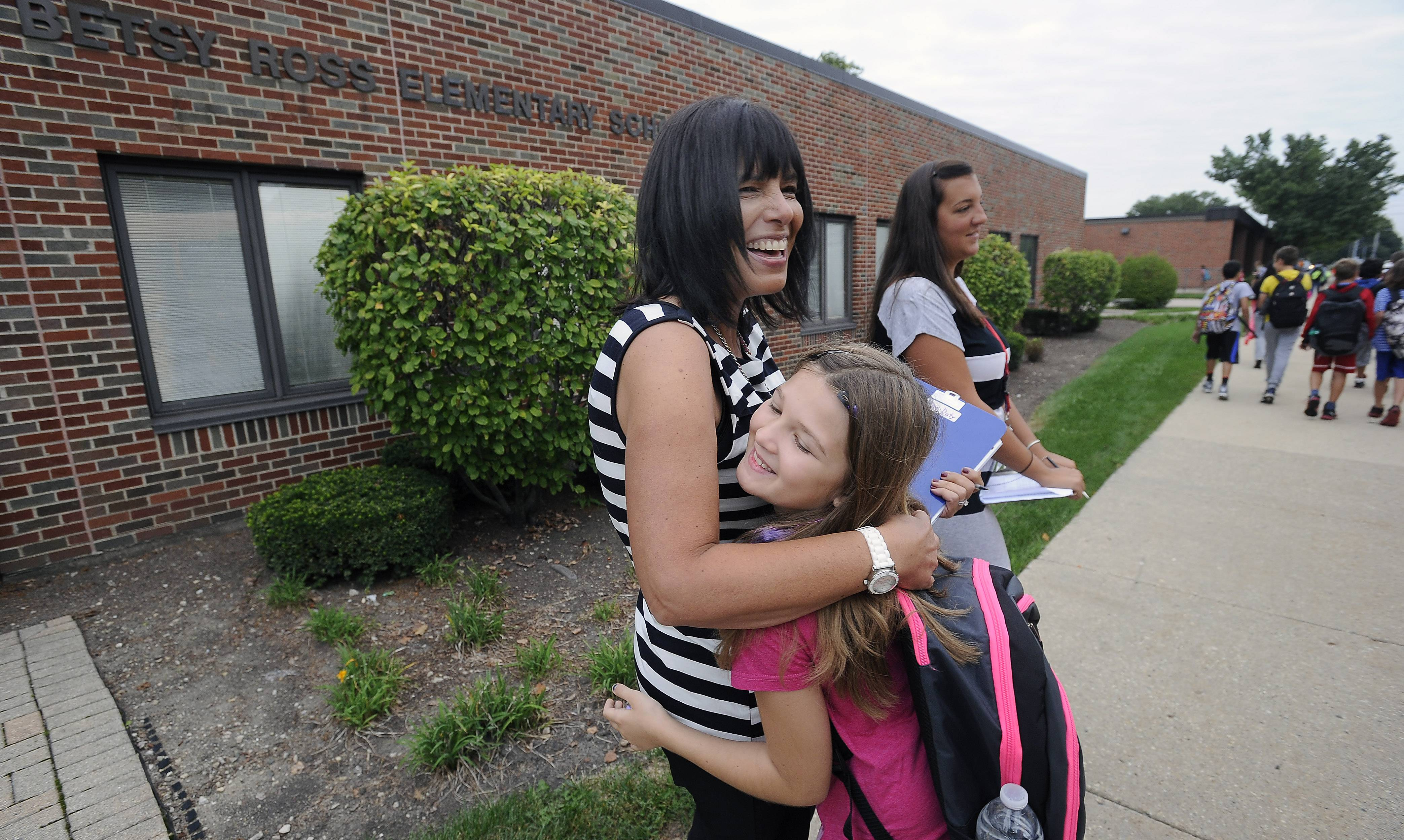 Debbie Crask, second grade assistant teacher, hugs Destiny Gillette, 9, who was heading back to the Anne Sullivan school after the strike in the District was settled over the weekend.