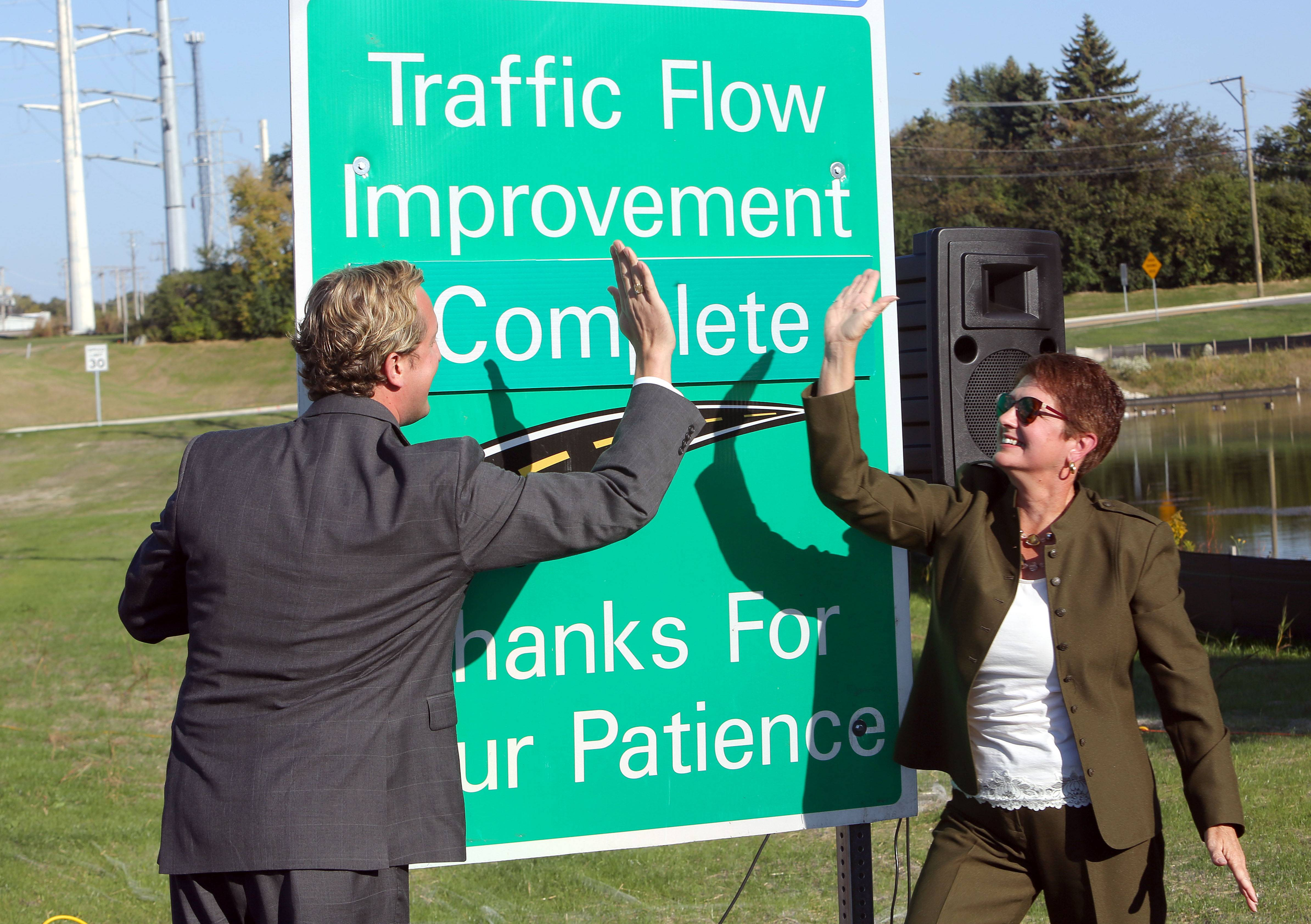 Lake County Board Chairman Aaron Lawlor, left, and Lake County Engineer Paula Trigg high-five Tuesday after marking the Rollins Road Gateway complete in Round Lake Beach.
