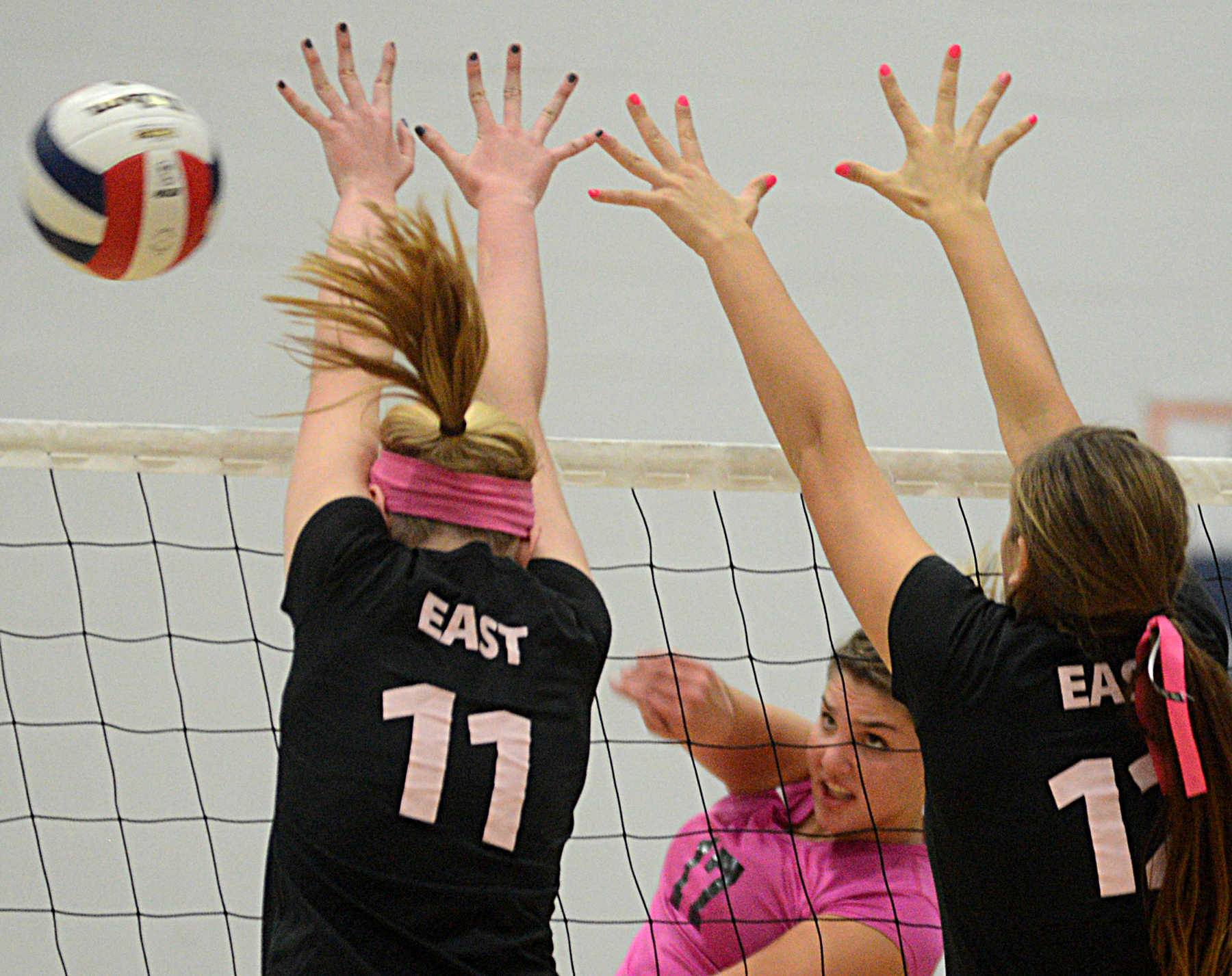 St. Charles North's Daley Krage, center, moves the ball past St. Charles East's Riley Schumacher, left, and Avery Macklin, right, during varsity girls volleyball at St. Charles North on Volley for the Cure night to honor and celebrate the heroic fight against breast cancer.