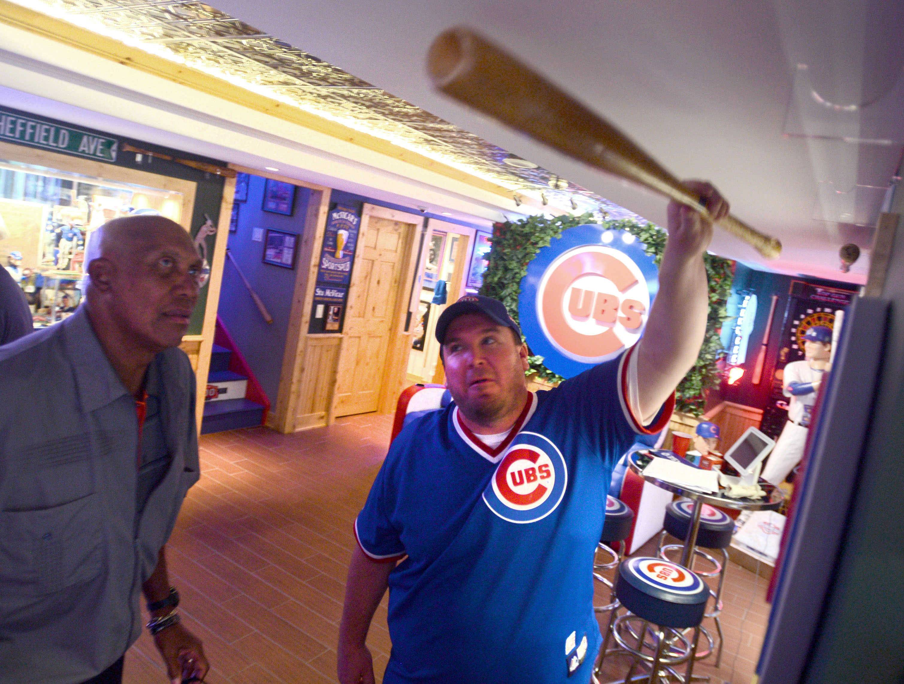 Stewart McVicar, center, hosted a party at his McHenry County home with Cubs legend and Hall-of-Famer Ferguson Jenkins in September. Here, Jenkins inspects one of his game-used bats from McVicar's memorabilia collection, which is displayed in McVicar's man cave.