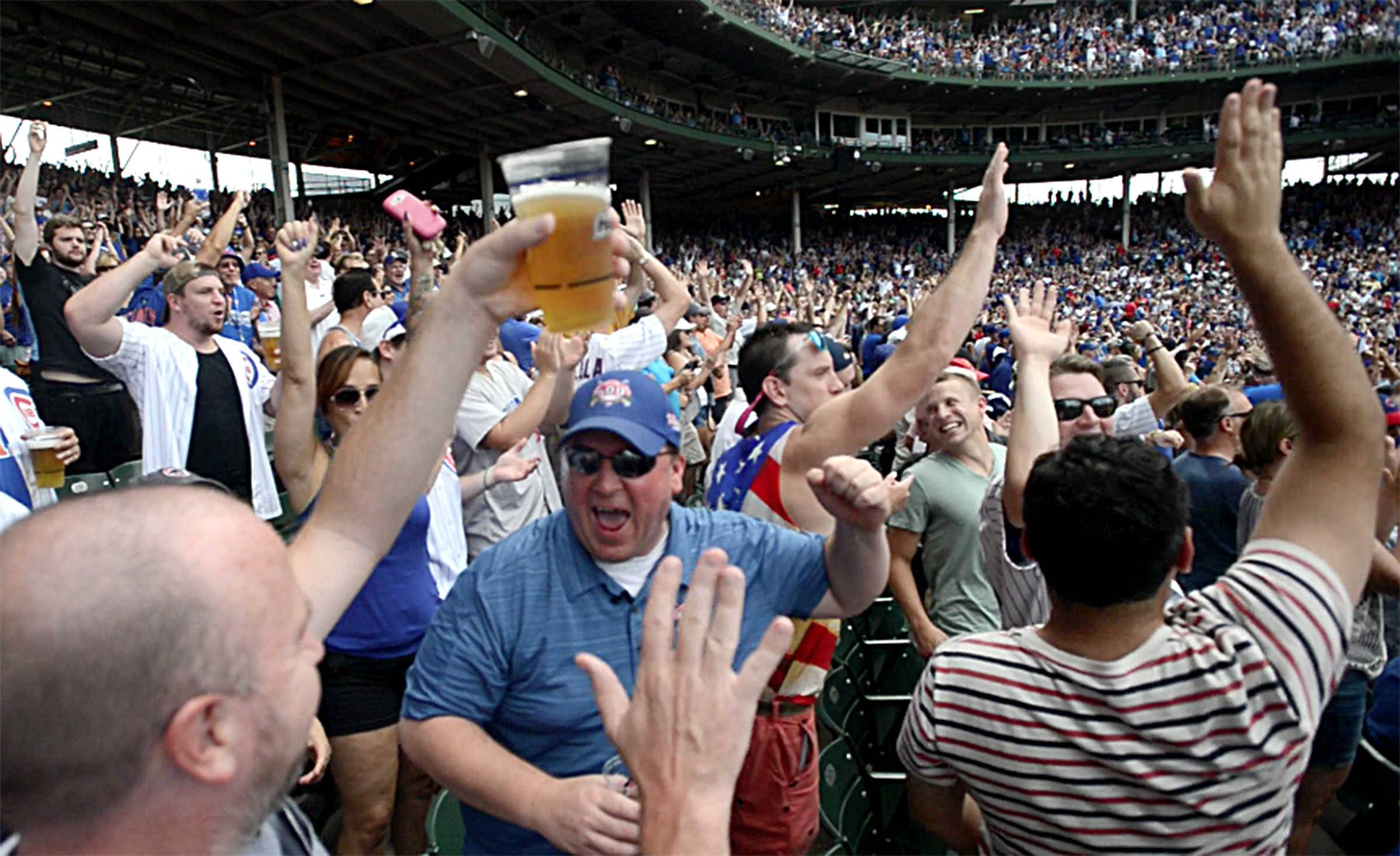 Cubs fan Stewart McVicar, center, celebrates an Anthony Rizzo home run during an Aug. 13 game at Wrigley Field in Chicago. At lower left is McVicar's good friend since childhood, Bob Cashin.
