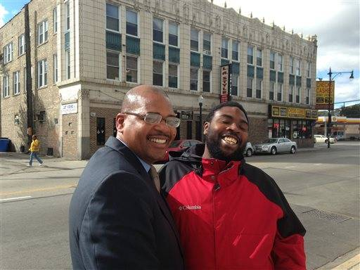 In this Sept. 30, 2015 photo, Autry Phillips, left, director of Target Area Development in Chicago's Auburn Gresham neighborhood, talks with area resident Justin Garner, 27, during a walk along 79th Street. Illinois Gov. Bruce Rauner froze funding for the anti-violence program Operation CeaseFire because of the state budget crisis, forcing Target Area and other organizations to shut down the program at a time of year when shootings spike. (AP Photo/Sara Burnett)