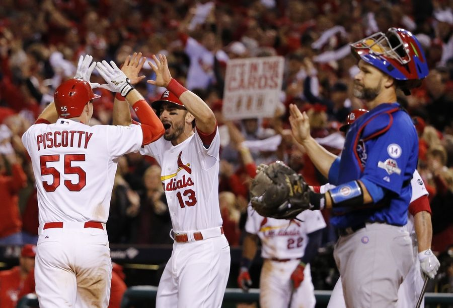 St. Louis Cardinals' Stephen Piscotty (55) celebrates with teammate Matt Carpenter after hitting a two-run home run during the eighth inning of Game 1 in baseball's National League Division Series against the Chicago Cubs, Friday, Oct. 9, 2015, in St. Louis. Cubs catcher David Ross, right, looks on.