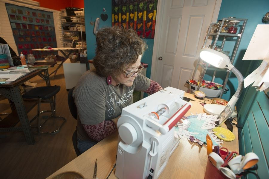 Lucy Dallman, a fiber artist, sews at her new Glen Ellyn studio, which also doubles as a gallery.