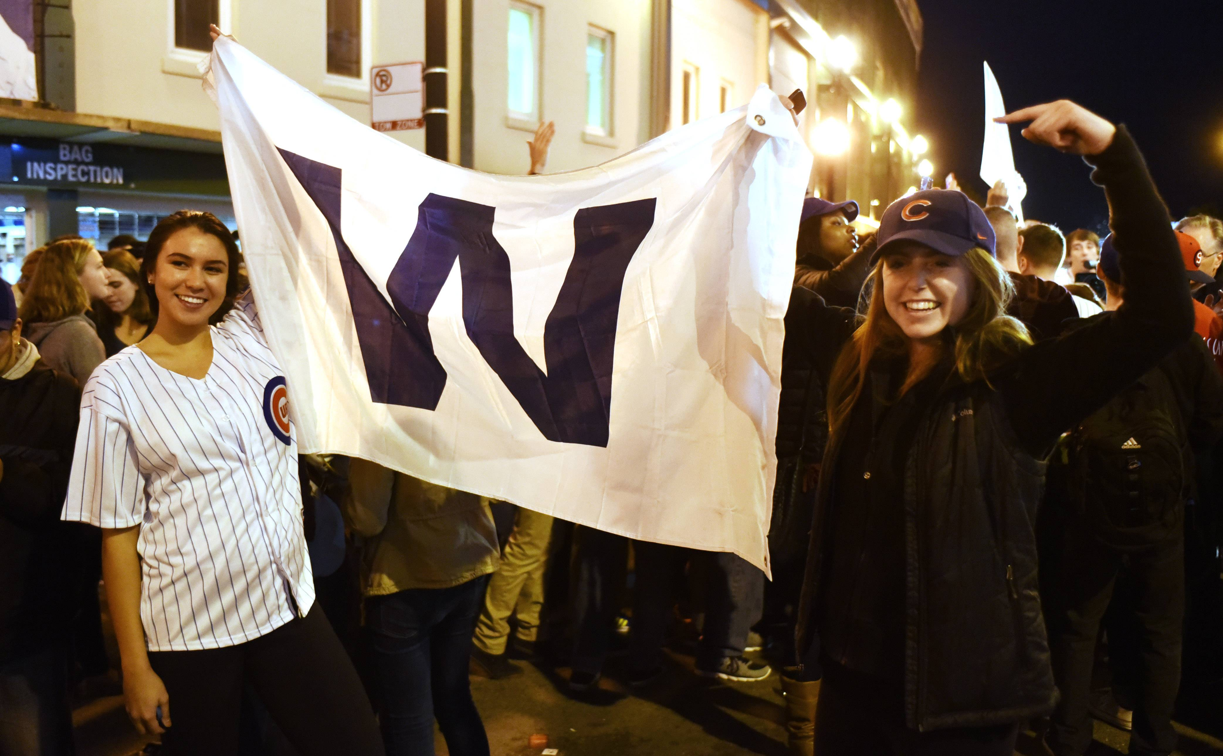 "Cubs fans hold the ""W"" flag following the team's Game 4 playoff victory over the St. Louis Cardinals at Wrigley Field Tuesday."