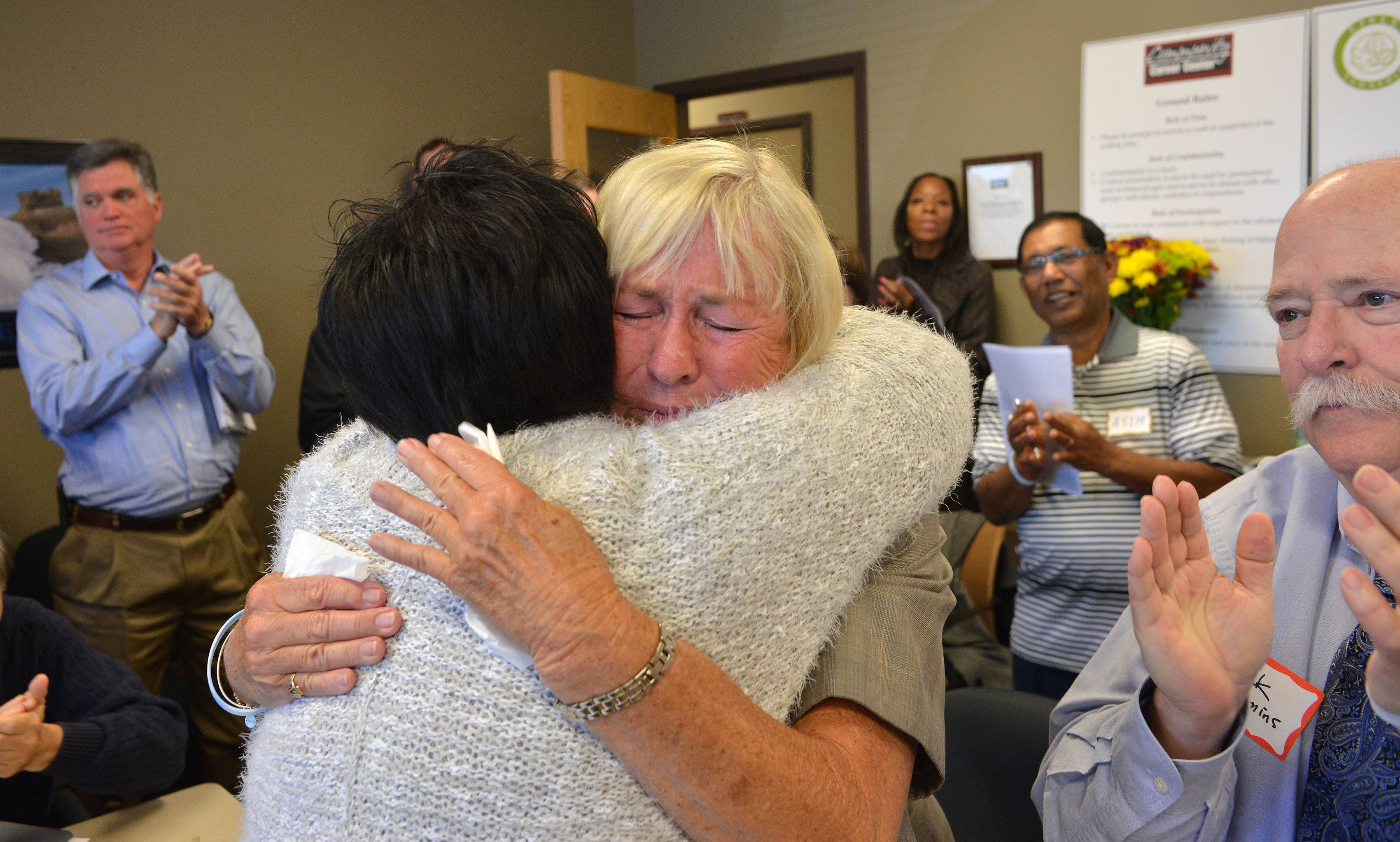 Joy Maguire Dooley, facing camera, gets an emotional send-off Wednesday at her final Job Club meeting at the Community Career Center in Naperville, which she helped found in 1996.