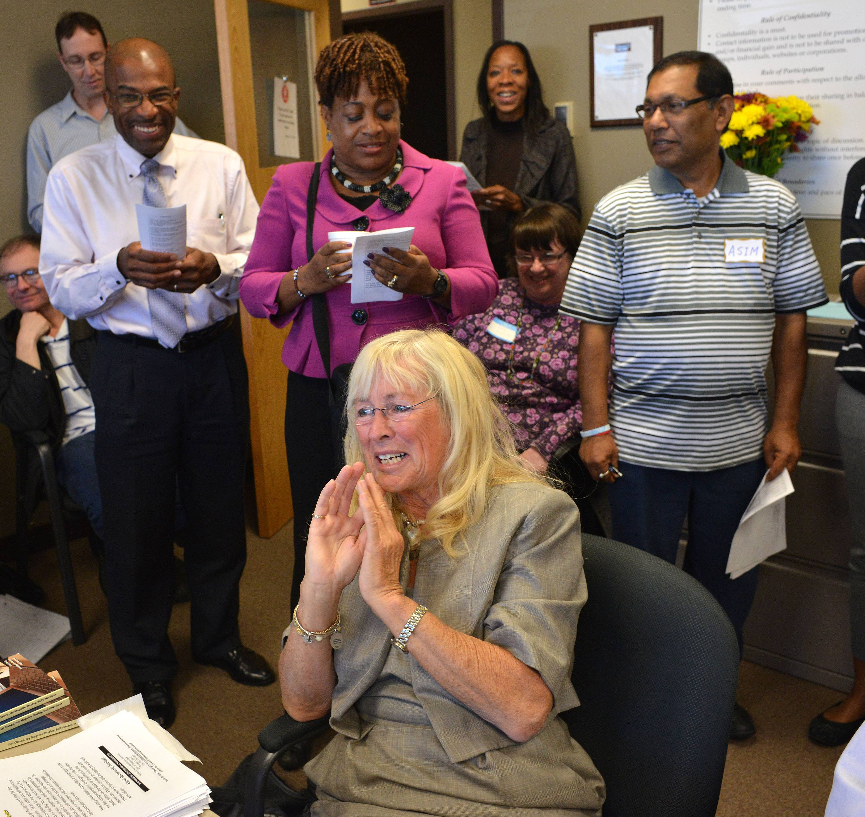 Joy Maguire Dooley, foreground, gets a surprise 'flash mob' send-off at her last Job Club meeting Wednesday. She is retiring after nearly 20 years of leading the Job Club at the Community Career Center in Naperville.