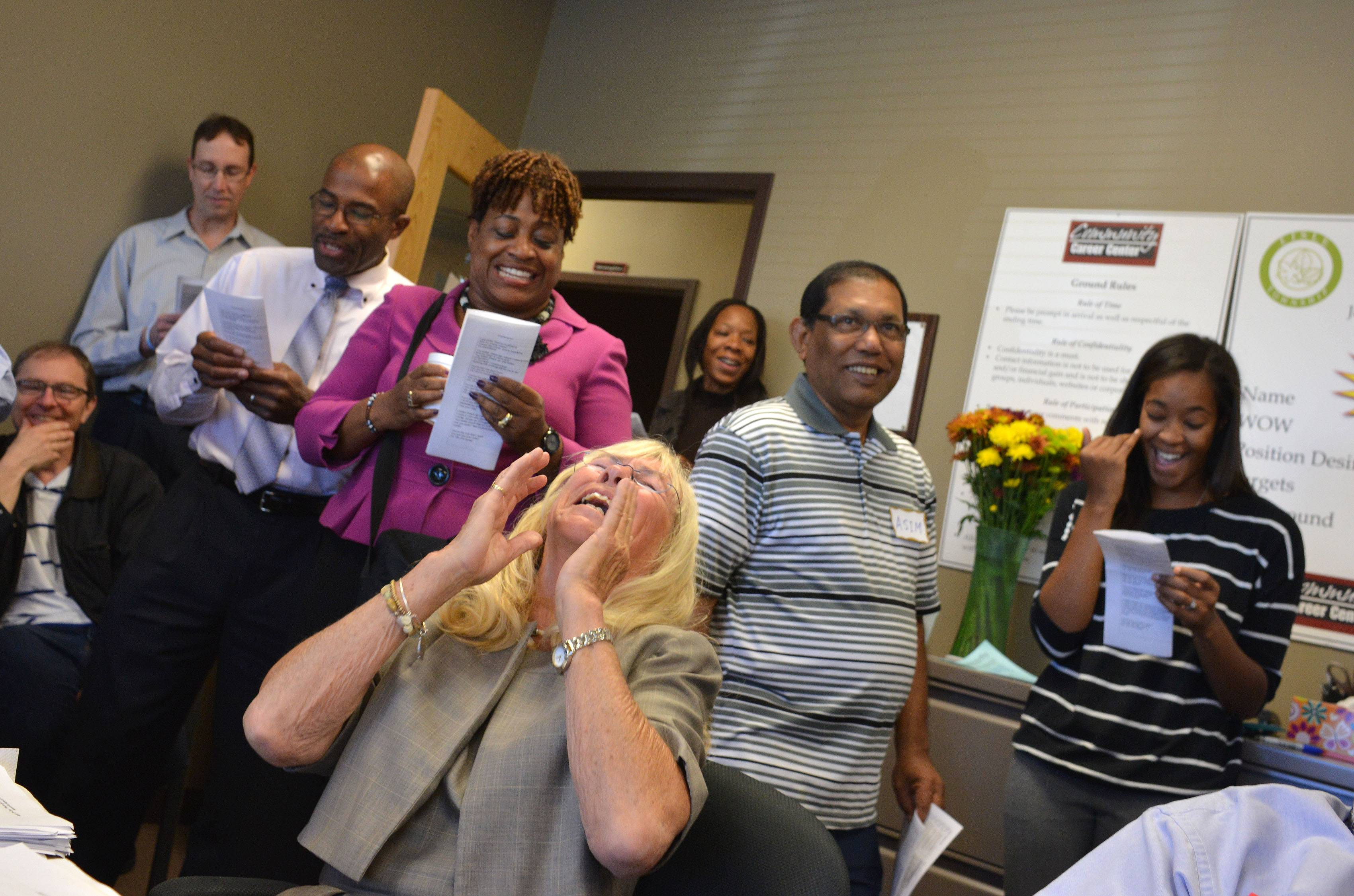 Joy Maguire Dooley, foreground, reacts after being surprised with a 'flash mob' at her last Job Club meeting Wednesday. She is retiring after nearly 20 years of leading the Job Club at the Community Career Center in Naperville, which she helped found.