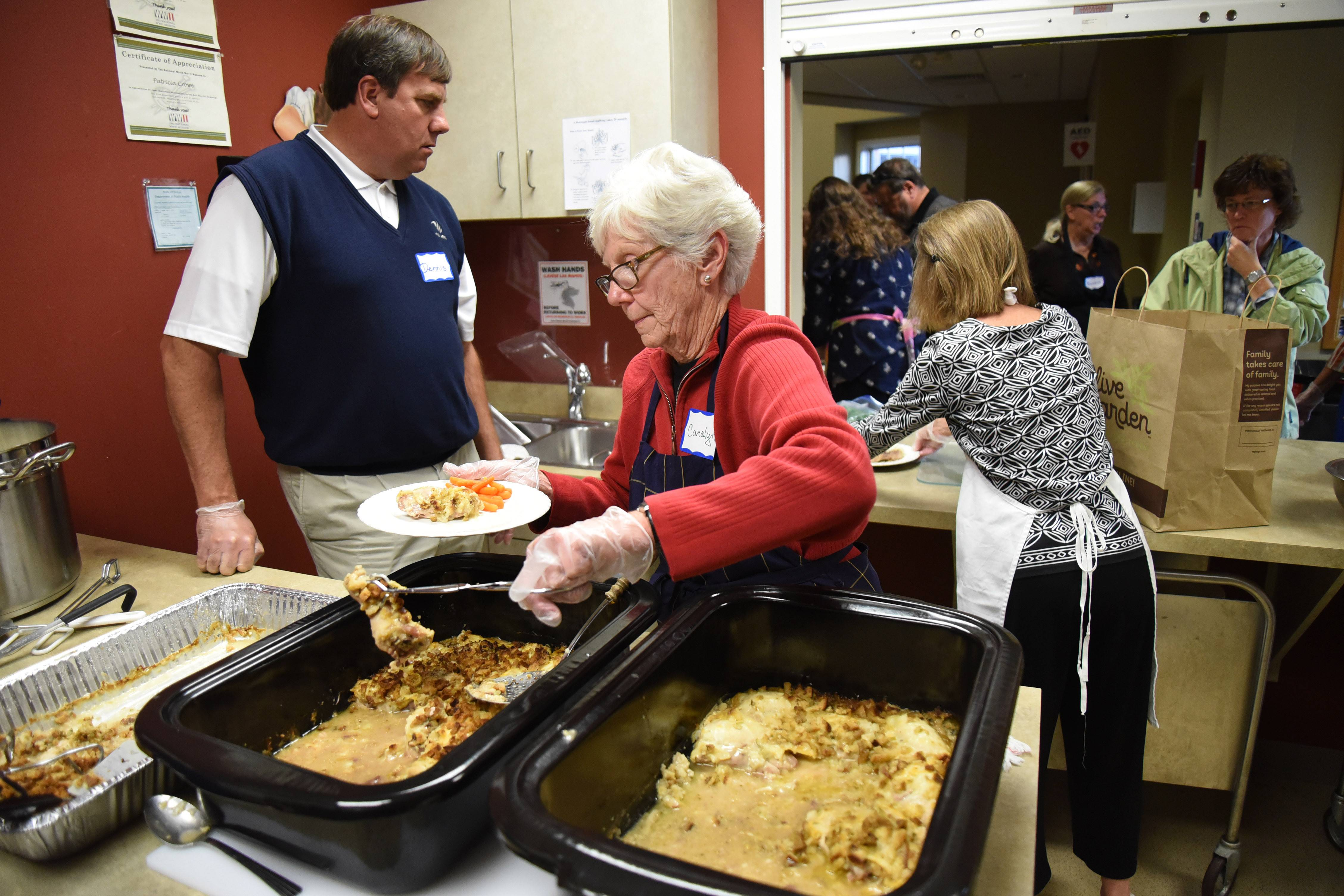 Carolyn Lortz of Elgin serves up a dinner plate with chicken as the First Congregational Church of Dundee hosts its first Hilltop Community Supper in West Dundee.
