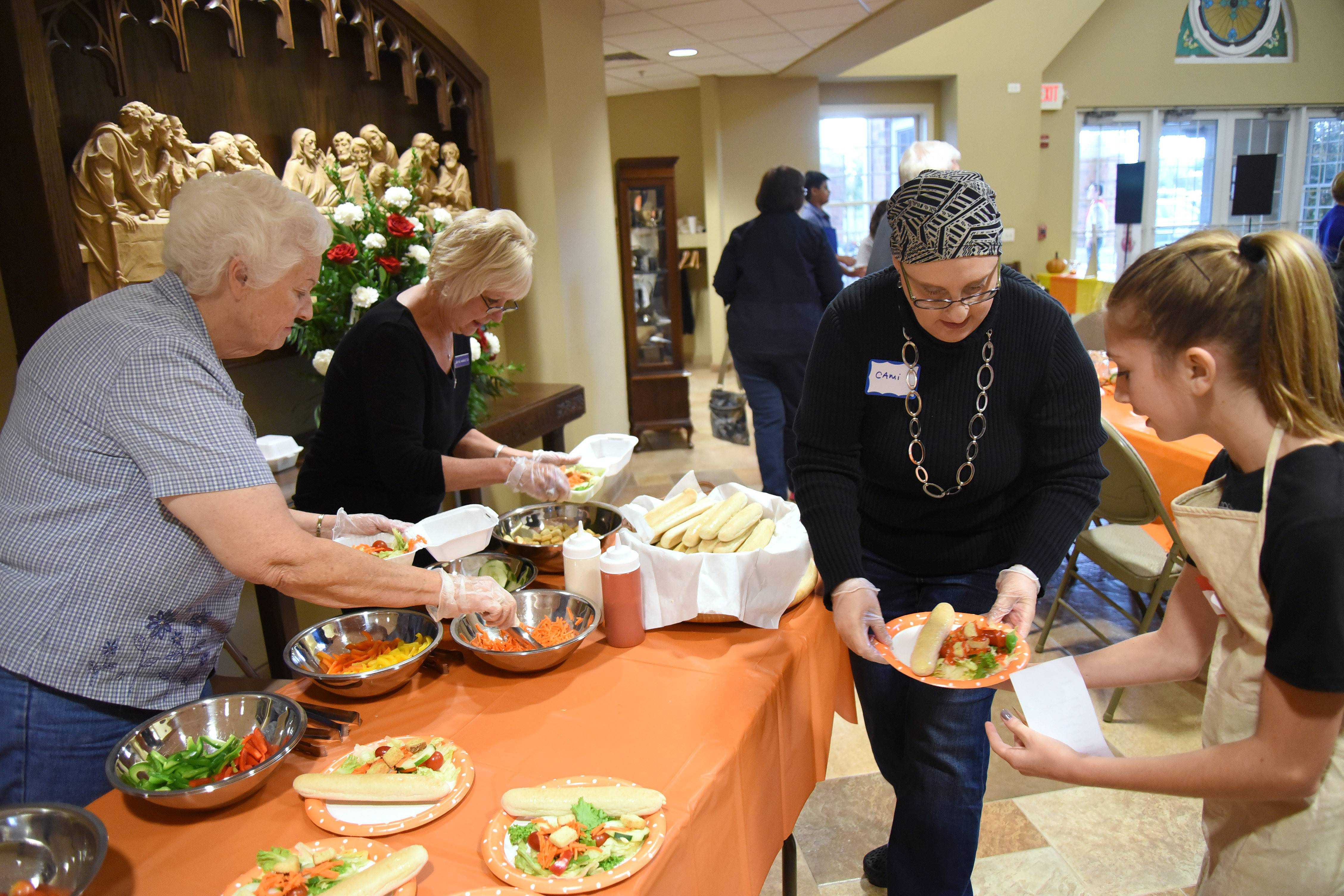 Left to right: Pat Storer of Huntley, Joanne Warkentien of West Dundee, Cami Bailey of Elgin and Alyson Doherty, 13, of West Dundee prep and serve salads as the First Congregational Church of Dundee hosts its first Hilltop Community Supper Tuesday in West Dundee.