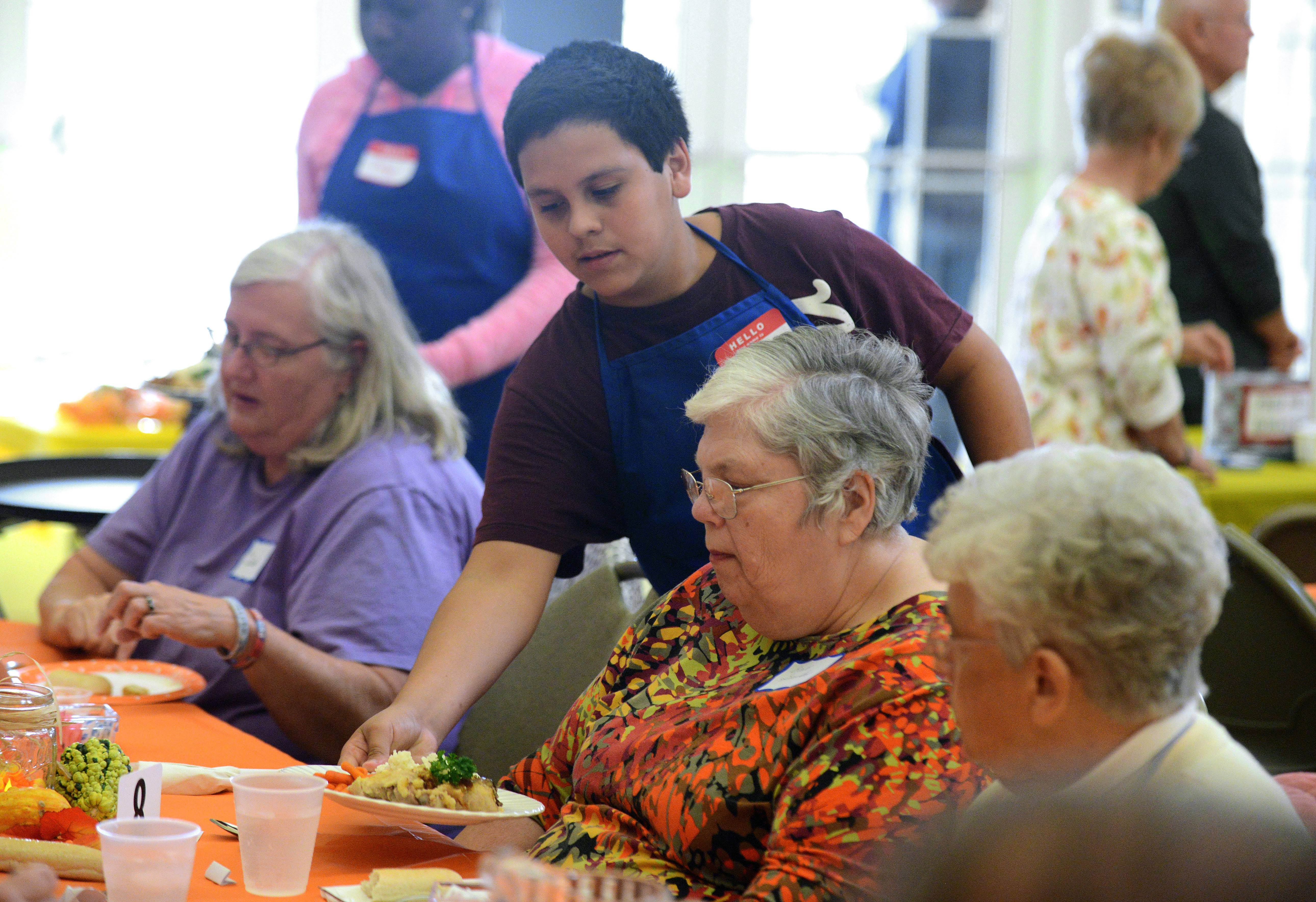 Volunteer Jose Alphonso, 12, of Carpentersville helps serve dinner at the Hilltop Community Supper hosted by First Congregational Church of Dundee in West Dundee.