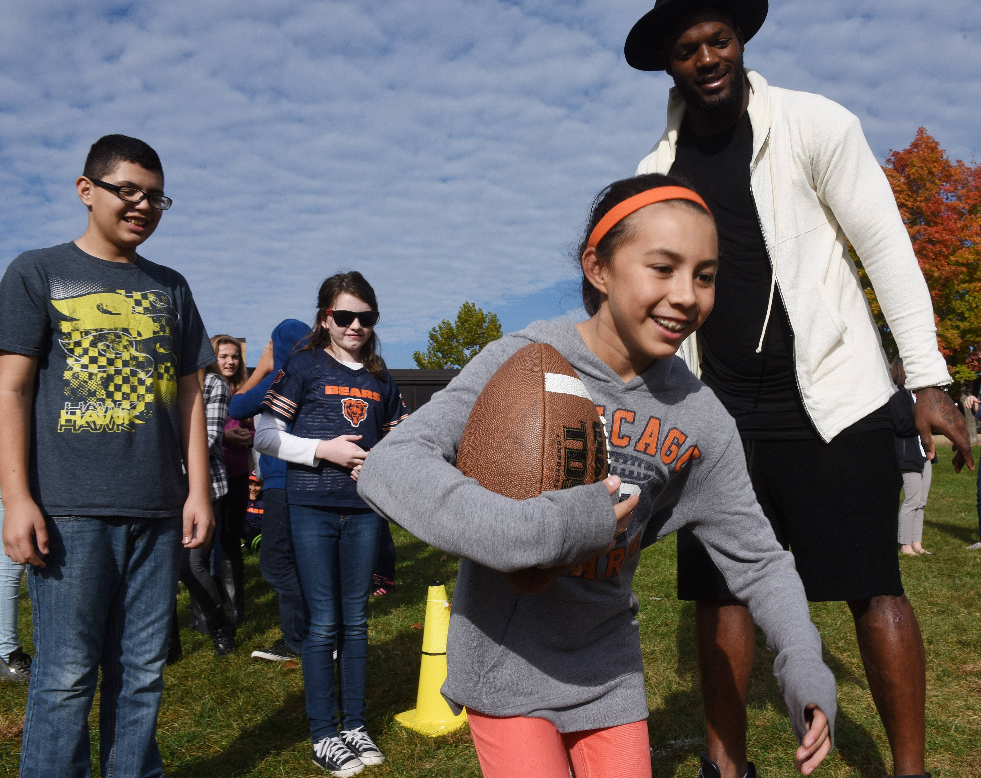 "Sixth-grader Abby Phillips takes a handoff from Chicago Bears tight end Martellus Bennett during a football drill Thursday at Stuart R. Paddock School in Palatine. Bennett and former NFL player turned author Tim Green visited the school as part of the NFL's ""Play60/Read20"" initiative."