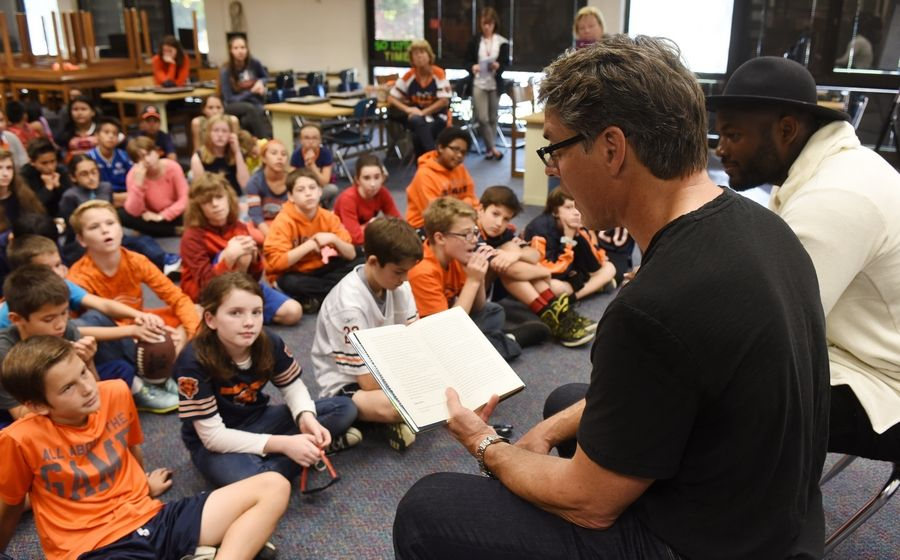 "Former NFL player and best-selling author Tim Green, left, and Chicago Bears tight end Martellus Bennett read from Green's new book, ""Kid Owner,"" on Thursday as part of the ""Play60/Read20"" initiative at Stuart R. Paddock School in Palatine."