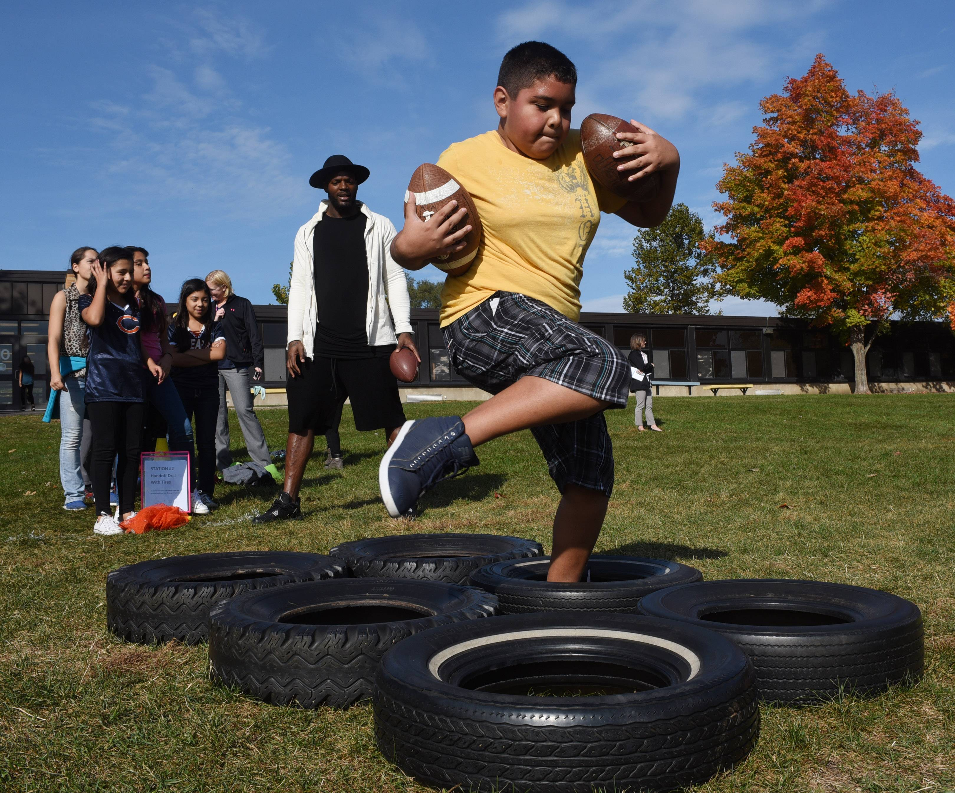 "Sixth-grader Adrian Montelongo carries two footballs Thursday after taking a handoff from Chicago Bears tight end Martellus Bennett as part of the NFL's ""Play60/Read20"" initiative at Stuart R. Paddock School in Palatine."