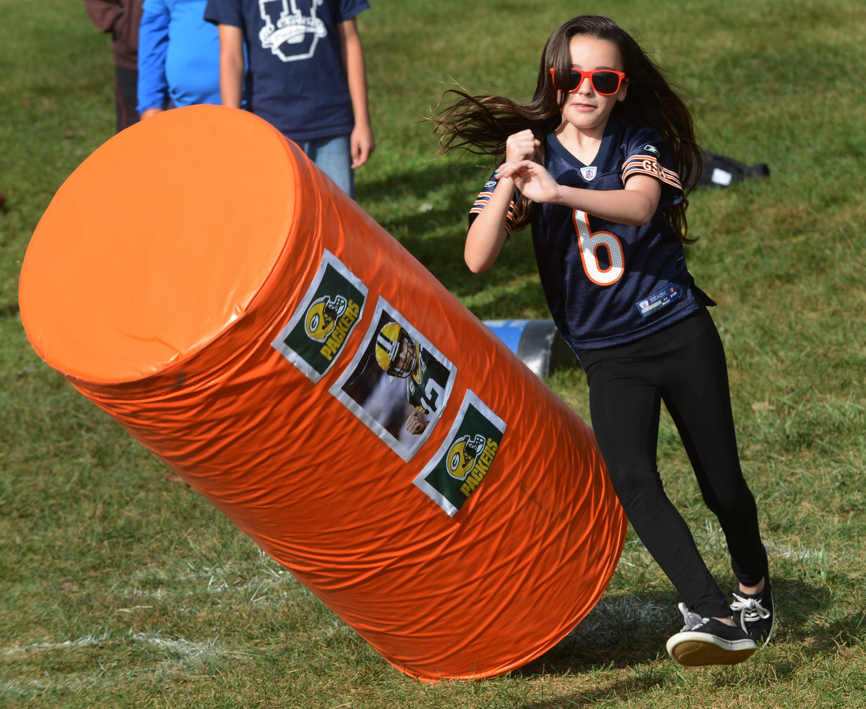 "Sixth-grader Katie Christopher looks for a fumble as she ""sacks the quarterback"" during a football drill as part of the NFL's ""Play60/Read20"" initiative at Stuart R. Paddock School in Palatine Thursday."
