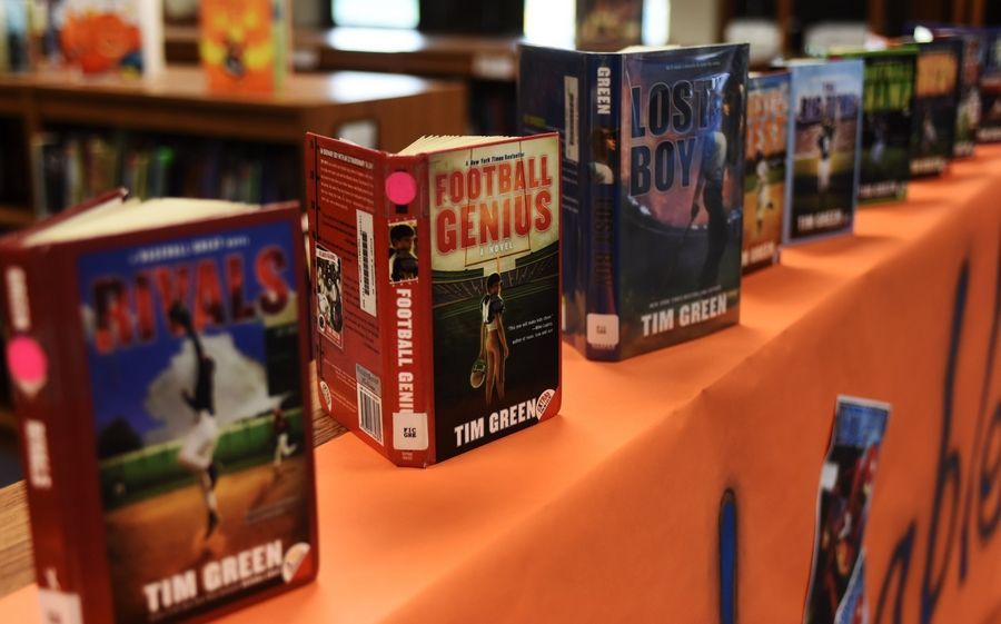Books by NFL veteran and best-selling author Tim Green are displayed at Stuart R. Paddock School library in Palatine Thursday.