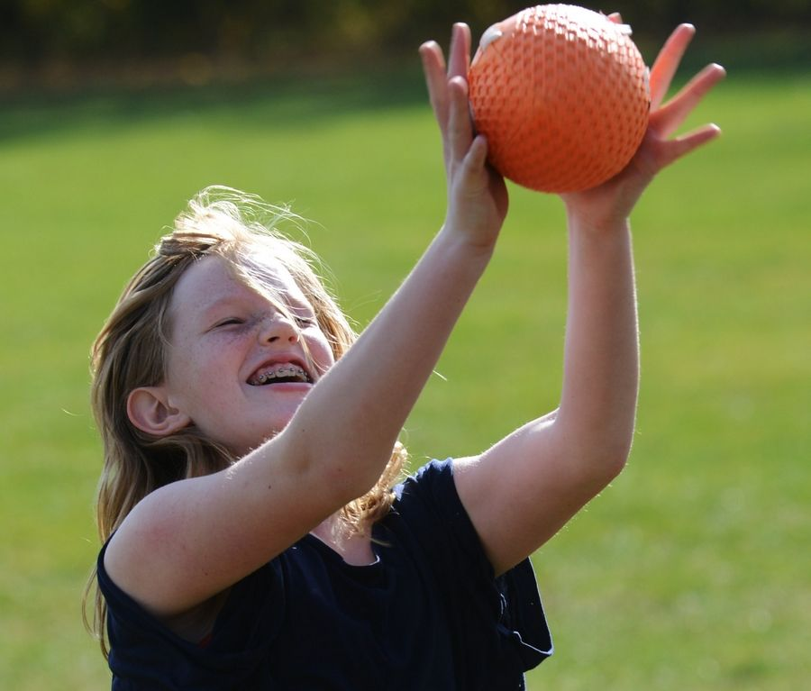 "Sixth-grader Delaney Garcea catches a pass during a football drill Thursday as part of the NFL's ""Play60/Read20"" initiative at Stuart R. Paddock School in Palatine."
