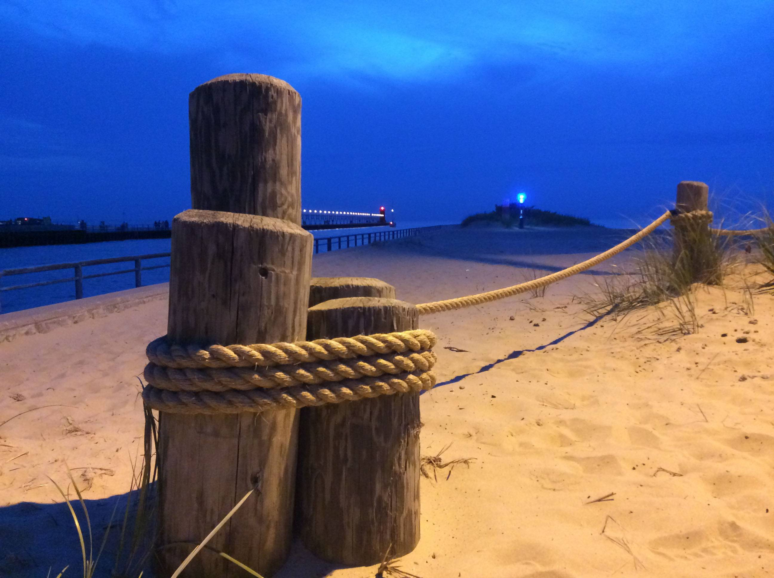 This photo is of pilings and the beach area at the South Haven Harbor Entrance in Michigan, shortly after sunset with clouds. I like the way the overhead light highlights the pilings, rope, and sand.