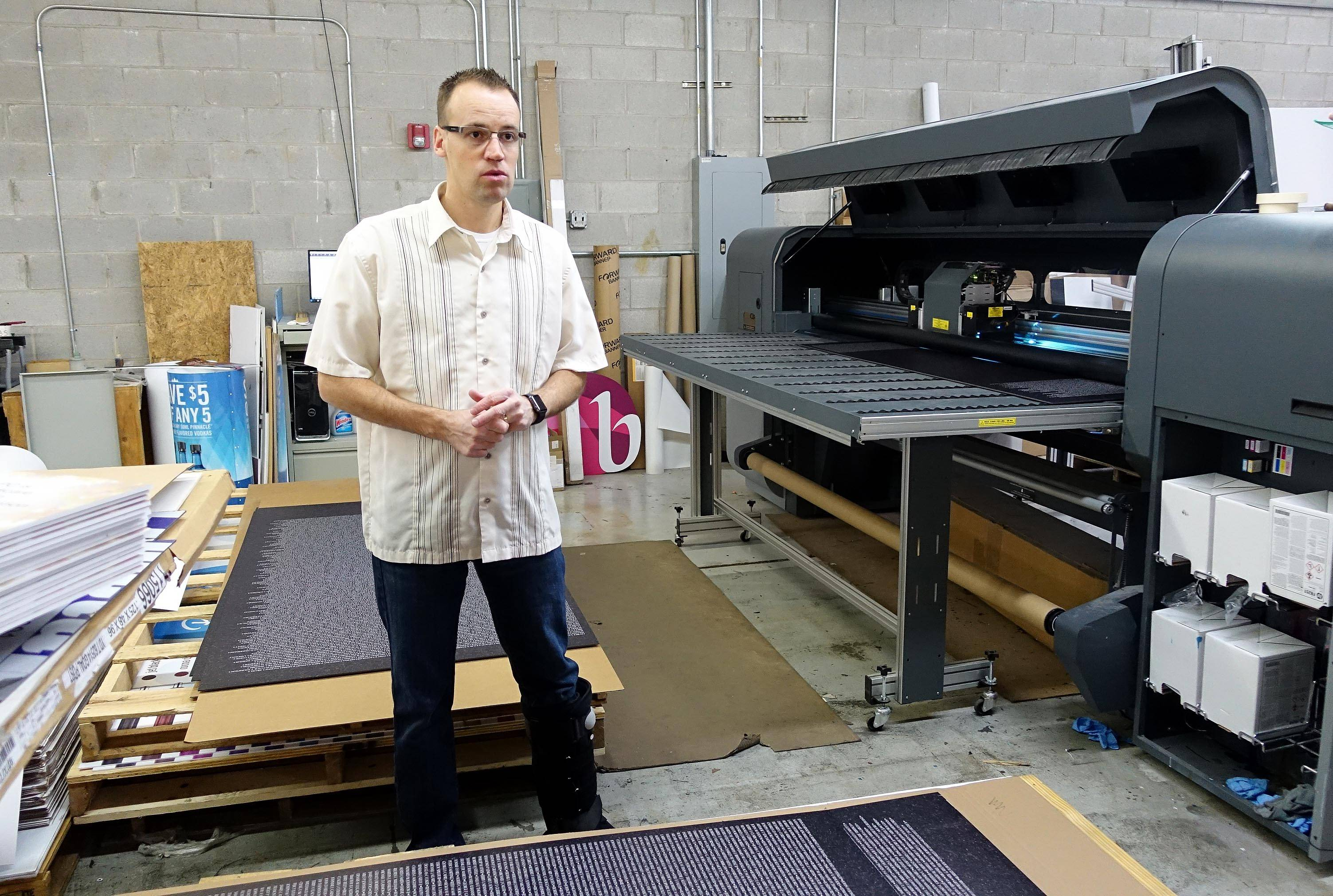 Brian Scott, president of Blooming Color in Lombard, explains how the company is printing a replica of the Vietnam Wall memorial in Washington, D.C., to be posted next month at the Healing Field of Honor in Naperville. The large inkjet printer to the right creates the names and background on each panel then dries the ink with UV lights.