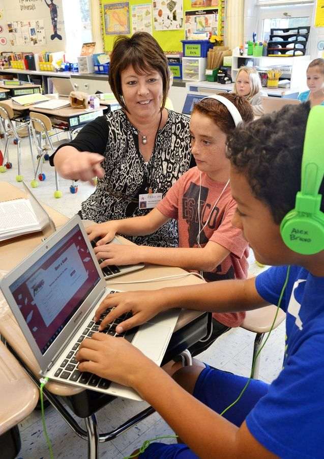 Fifth-grade teacher Gillian Wilson works with Myles James, center, and Alex Bravo on their keyboarding skills at Emerson Elementary in Wheaton. The school is one of only 13 in Illinois to be designated a 2015 National Blue Ribbon School.