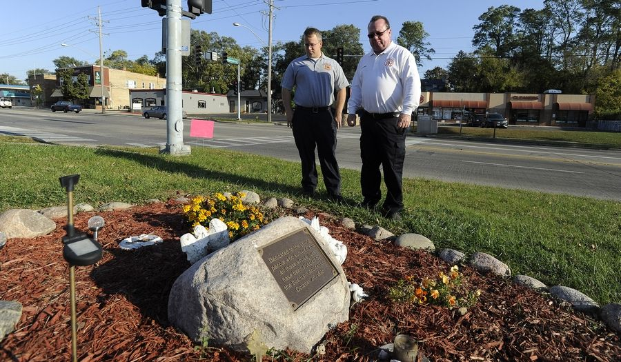 Fox River Grove Fire Capt. Jason Kedrok, left, and Fire Chief Bob Kreher pause at the memorial at the site where a train struck a school bus in 1995, killing seven students. Kedrok was on the bus that day and Kreher was one of the emergency workers at the scene.
