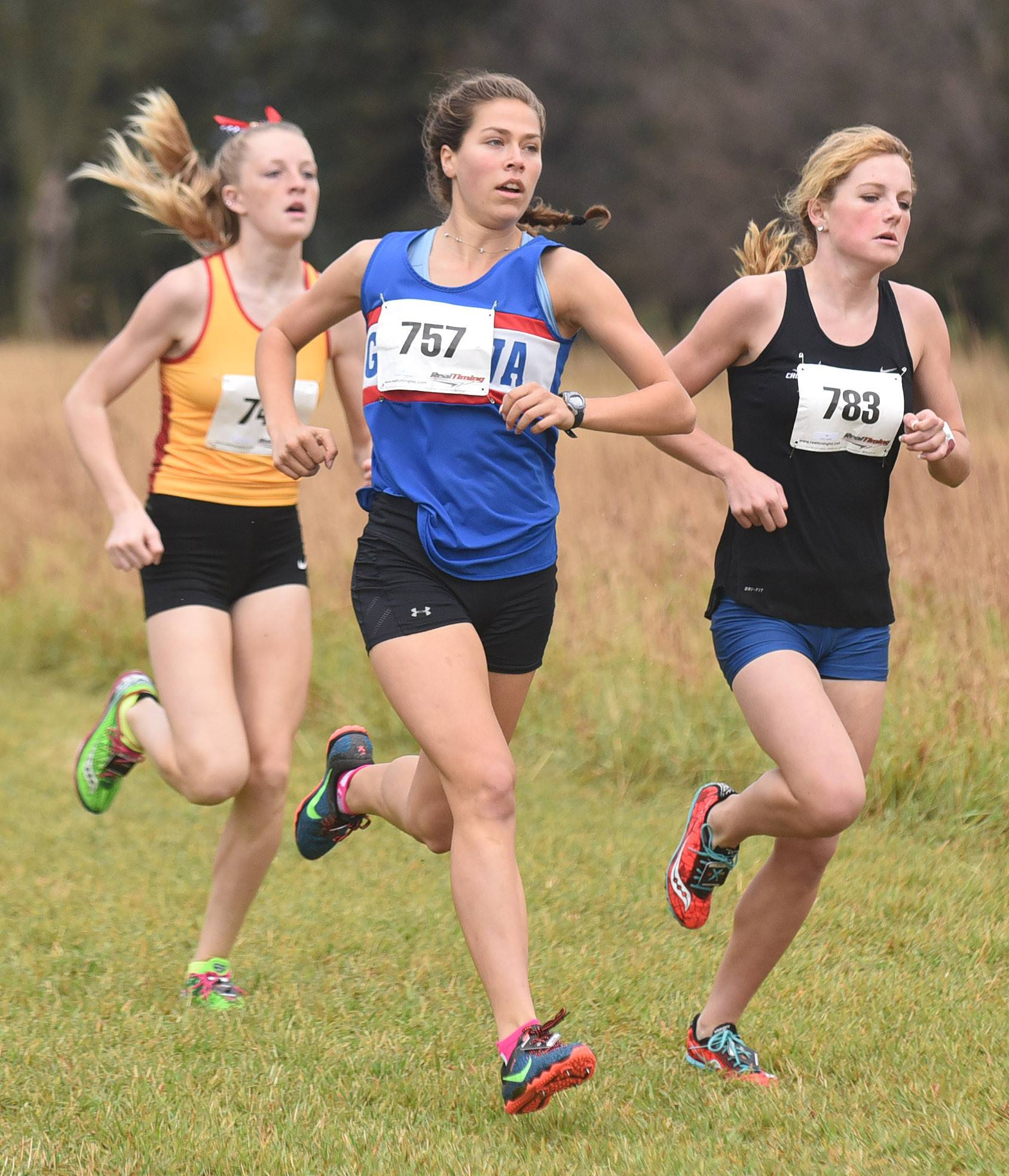 Geneva's McKenzie Altmayer (757) leads the start of the girls varsity race flanked by Batavia's Emma Stephens, left, and St. Charles North's Audrey Ernst (783) at the St. Charles North cross country regional on Saturday. Altmayer took first place.