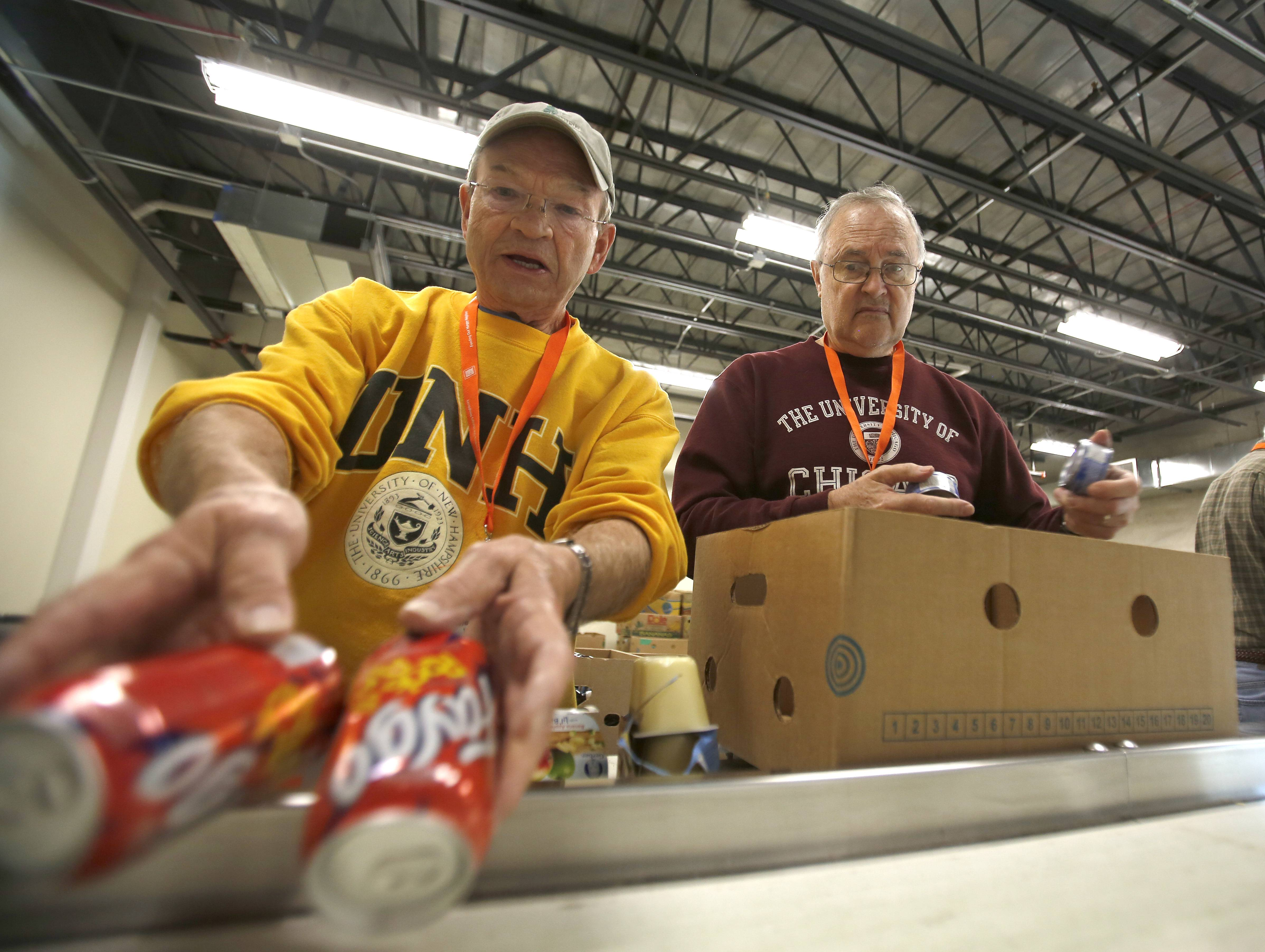 Duane Wickstrom, left, and Dan Edwards, both of Geneva, are regular volunteers at the Northern Illinois Food Bank headquarters in Geneva. They are packing food collected in charity drives, for distribution to pantries in 13 counties in northern Illinois.