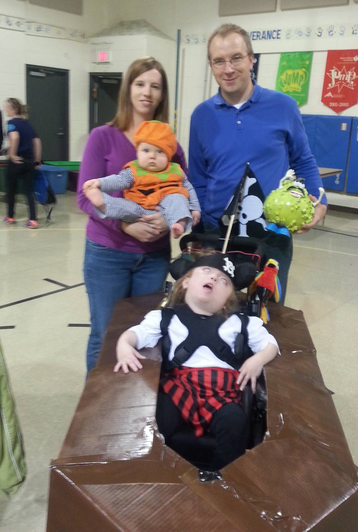 Using cardboard, duct tape and spray paint, Willie and Kelly Hedrick of Elk Grove Village turn the wheelchair used by their daughter, Kaitylyn, into an awesome pirate ship so she can celebrate Halloween with her little sister, Alyssa, wearing the pumpkin suit.