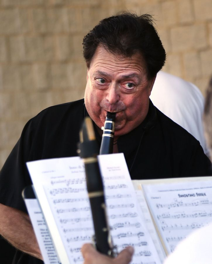 Conductor Ralph Wilder warms up on the clarinet as the Mount Prospect Community Band gets ready to perform at Veterans´ Memorial Band Shell in Lions Park Monday night in Mount Prospect.