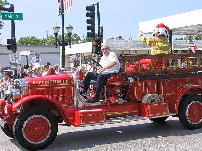 Lt. James Feit drives an antique firetruck during the Barrington Fourth of July parade.