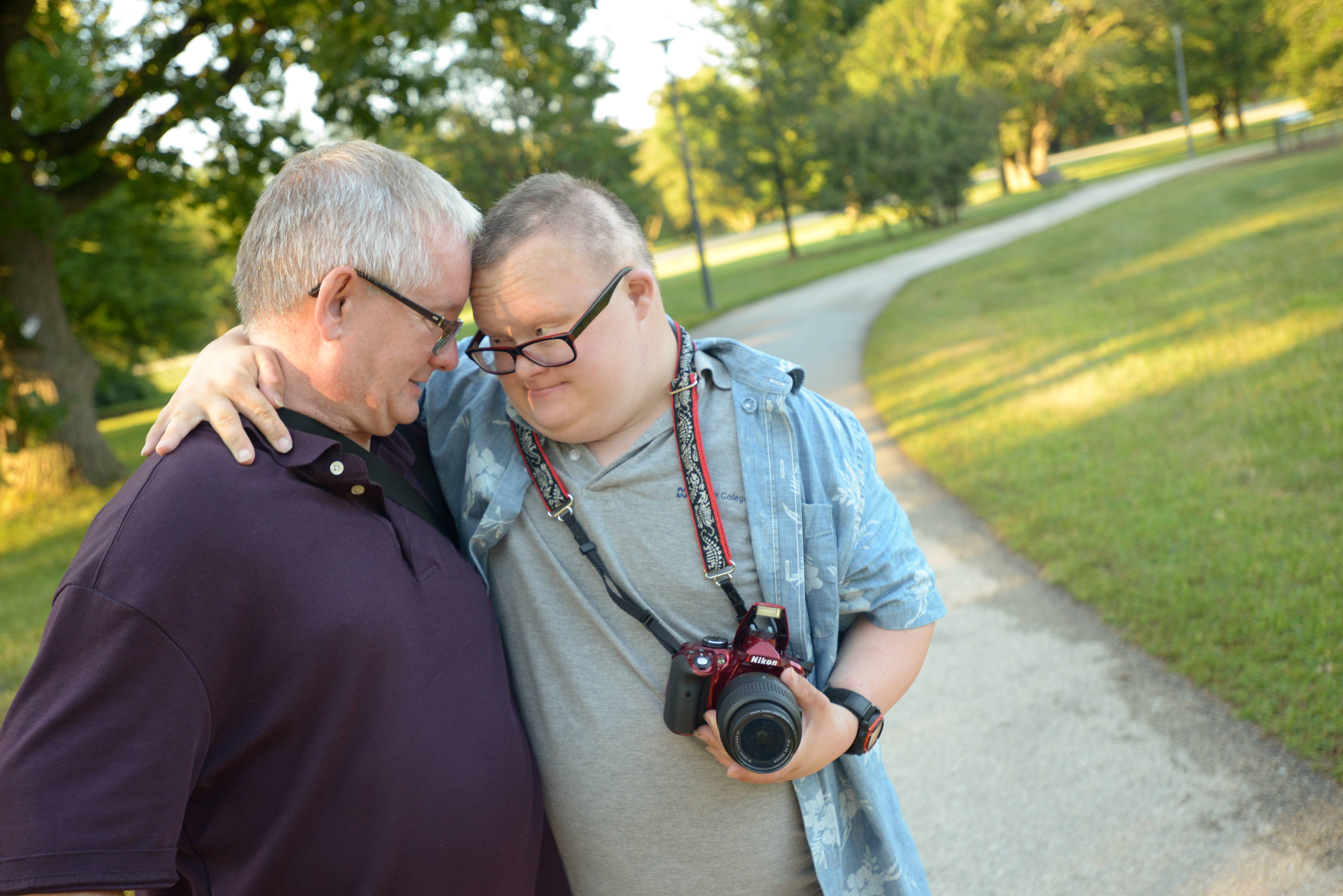Geoffrey Mikol gives his dad Paul a hug while on a photography outing in the Morton Arboretum.