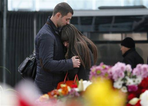 A couple stands next to flowers and toys at an entrance of Pulkovo airport outside St. Petersburg, Russia, during a day of national mourning for the victims of Saturday's plane crash over Egypt Wednesday, Nov. 4, 2015. A Russian official says families have identified the bodies of 33 victims killed in the disaster. The Russian jet crashed over the Sinai Peninsula early Saturday, killing all 224 people on board. Most of them were holidaymakers from Russia's St. Petersburg.