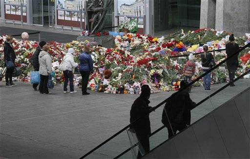 People stand near to floral tributes for the victims of a plane crash, at an entrance of Pulkovo airport outside St. Petersburg, Russia, Wednesday, Nov. 4, 2015. A Russian official says families have identified the bodies of 33 victims killed in Saturday's plane crash over Egypt. The Russian jet crashed over the Sinai Peninsula early Saturday, killing all 224 people on board. Most of them were holidaymakers from Russia's St. Petersburg.
