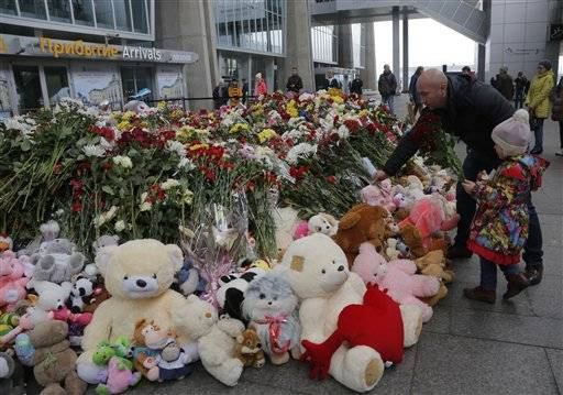 A man and his daughter put flowers and a toy at an entrance of Pulkovo airport outside St.Petersburg, Russia, Wednesday, Nov. 4, 2015. A Russian official says families have identified the bodies of 33 victims killed in Saturday's plane crash over Egypt. The Russian jet crashed over the Sinai Peninsula early Saturday, killing all 224 people on board. Most of them were holidaymakers from Russia's St. Petersburg.