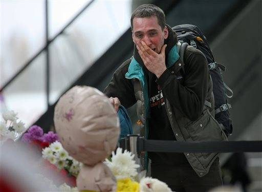 A man reacts as he stands next to flowers and toys at an entrance of Pulkovo airport outside St. Petersburg, Russia during a day of national mourning for the victims of Saturday's plane crash over Egypt Wednesday, Nov. 4, 2015. A Russian official says families have identified the bodies of 33 victims killed in the disaster. The Russian jet crashed over the Sinai Peninsula early Saturday, killing all 224 people on board. Most of them were holidaymakers from Russia's St. Petersburg.