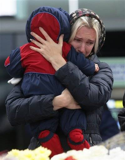 A woman with her baby reacts as she stands near to floral tributes for the victims of a plane crash, at an entrance of Pulkovo airport outside St. Petersburg, Russia, Wednesday, Nov. 4, 2015. A Russian official says families have identified the bodies of 33 victims killed in Saturday's plane crash over Egypt. The Russian jet crashed over the Sinai Peninsula early Saturday, killing all 224 people on board. Most of them were holidaymakers from Russia's St. Petersburg.