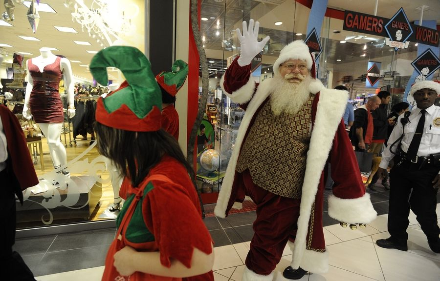 Santa walks around Woodfield Mall with the help of the Conant Marching Band as he arrived early from the North Pole to listen to all the wishes of the good boys and girls.