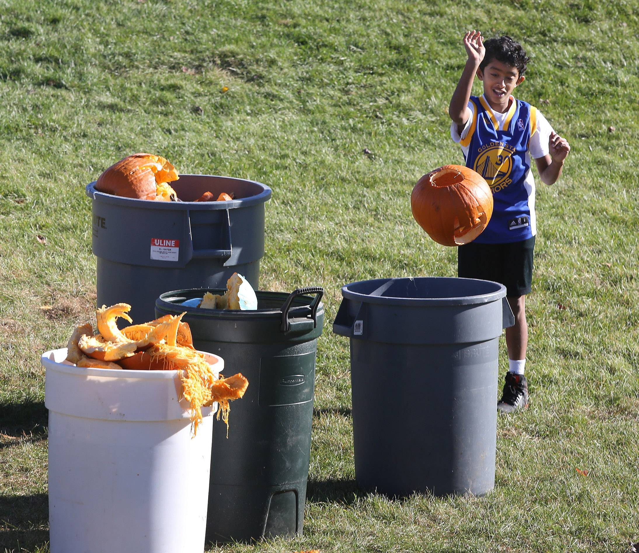 Keshav Chandramouli, 9, of Mundelein throws a pumpkin in a garbage can after the 8th annual Pumpkin Drop Sunday at Keith Mione Community Park in Mundelein. The leftover pumpkin scraps from the event were collected and sent to the Prairie Crossing farm in Grayslake for composting.