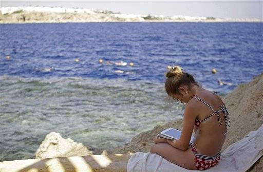 A Russian tourists reads a book by the shore of the Red Sea at a hotel that is hosting many travelers waiting to be evacuated from the resort city of Sharm el-Sheikh, south Sinai, Egypt, Saturday, Nov. 7, 2015. Russia has suspended all flights to Egypt, joining the U.K., which had specifically banned all flights to the resort city in response to a Russian plane crash last week in Egypt's Sinai. Empty charter planes have been flying to the resort to bring home stranded Russian and British tourists.