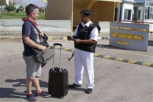 An Egyptian policeman checks a Russian tourist's passport at the main entrance to the Sharm el-Sheikh airport in Egypt on Saturday, Nov. 7, 2015. Egypt's Foreign Minister Sameh Shoukry complained on Saturday that Western governments had not sufficiently helped Egypt in its war on terrorism and had not shared relevant intelligence with Cairo regarding the Russian airplane that crashed last week in the Sinai, killing all 224 people onboard.