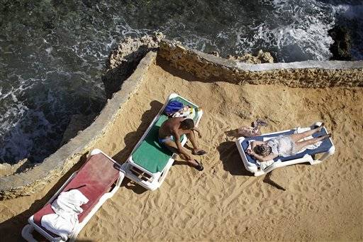 Tourists sunbathe on the shore of the Red Sea at a hotel that is hosting many travelers waiting to be evacuated from the resort city of Sharm el-Sheikh, south Sinai, Egypt, Saturday, Nov. 7, 2015. Russia has suspended all flights to Egypt, joining the U.K., which had specifically banned all flights to the resort city in response to a Russian plane crash last week in Egypt's Sinai. Empty charter planes have been flying to the resort to bring home stranded Russian and British tourists.