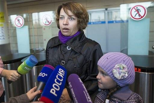 A traveller arrived from Hurghada, speaks to the media at Domodedovo airport in Moscow, Saturday, Nov. 7, 2015. Russia has banned all flights to Egypt until aviation security procedures improve but was allowing special flights to bring Russian tourists back home from Sharm el-Sheikh. A Russian Airbus A321-200 crashed 23 minutes after takeoff from the resort on Oct. 31, killing all 224 people on board.