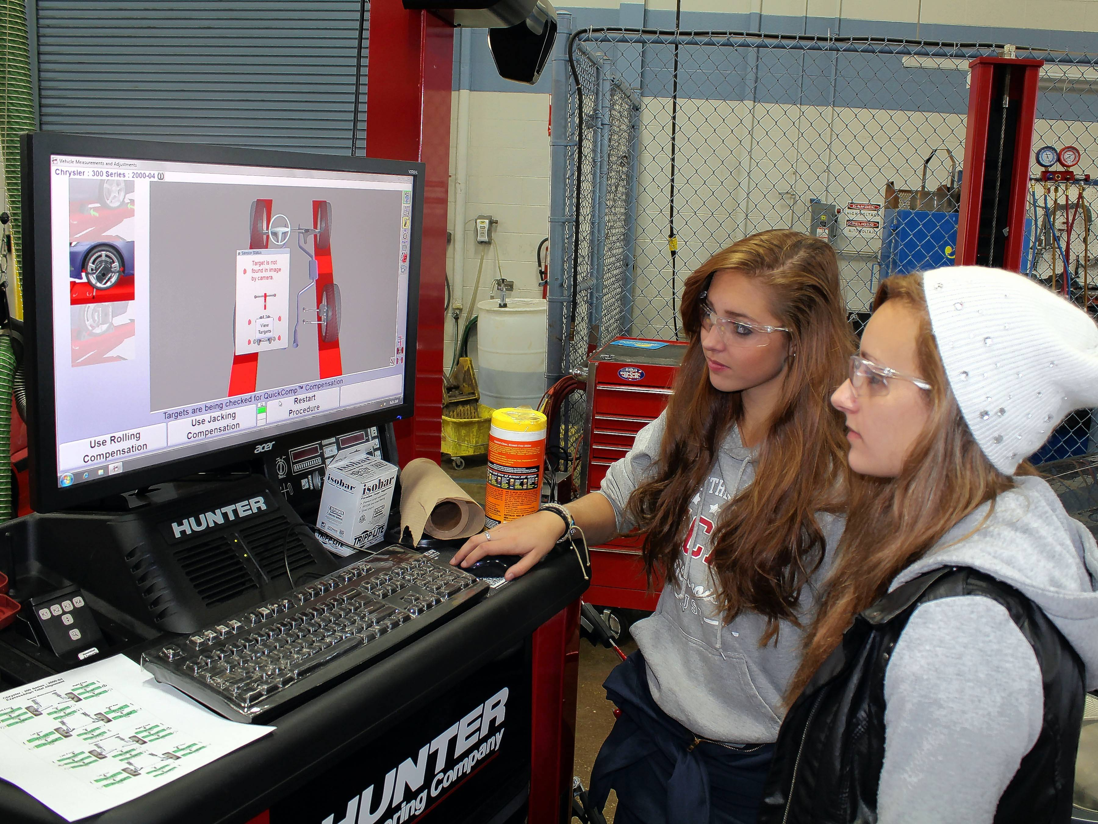High school seniors Lauren Mirabella, left, and Cayla Fuechsl use advanced diagnostic technology that employs cameras and lasers to help technicians do alignments. The two are among eight female auto tech students enrolled this year at Technology Center of DuPage, an elective part their high school curriculum.