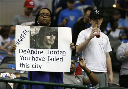 A fan in the stands holds up a sign during the first half of an NBA basketball game between the Los Angeles Clippers and Dallas Mavericks Wednesday, Nov. 11, 2015, in Dallas. DeAndre Jordan verbally committed to leaving the Clippers for the Mavericks before this season, but then decided to stay with the Clippers.