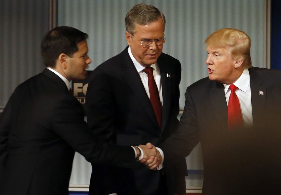 Marco Rubio and Donald Trump shake hands in front of Jeb Bush during Republican presidential Tuesday in Milwaukee.