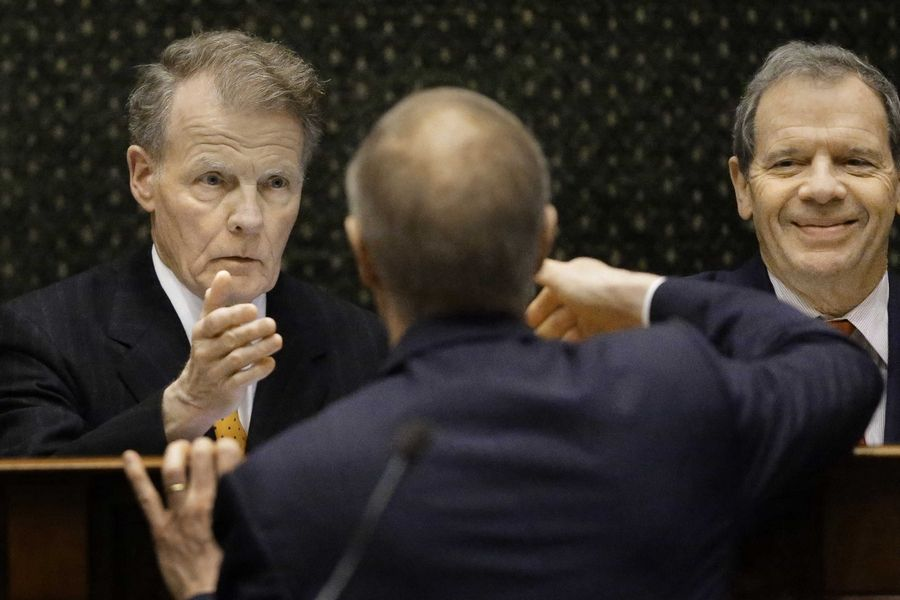 Illinois Gov. Bruce Rauner, center, reaches to shake the hand of Illinois Speaker of the House Michael Madigan left last February after giving a speech to the Legislature. Madigan won't attend a budget meeting Wednesday.