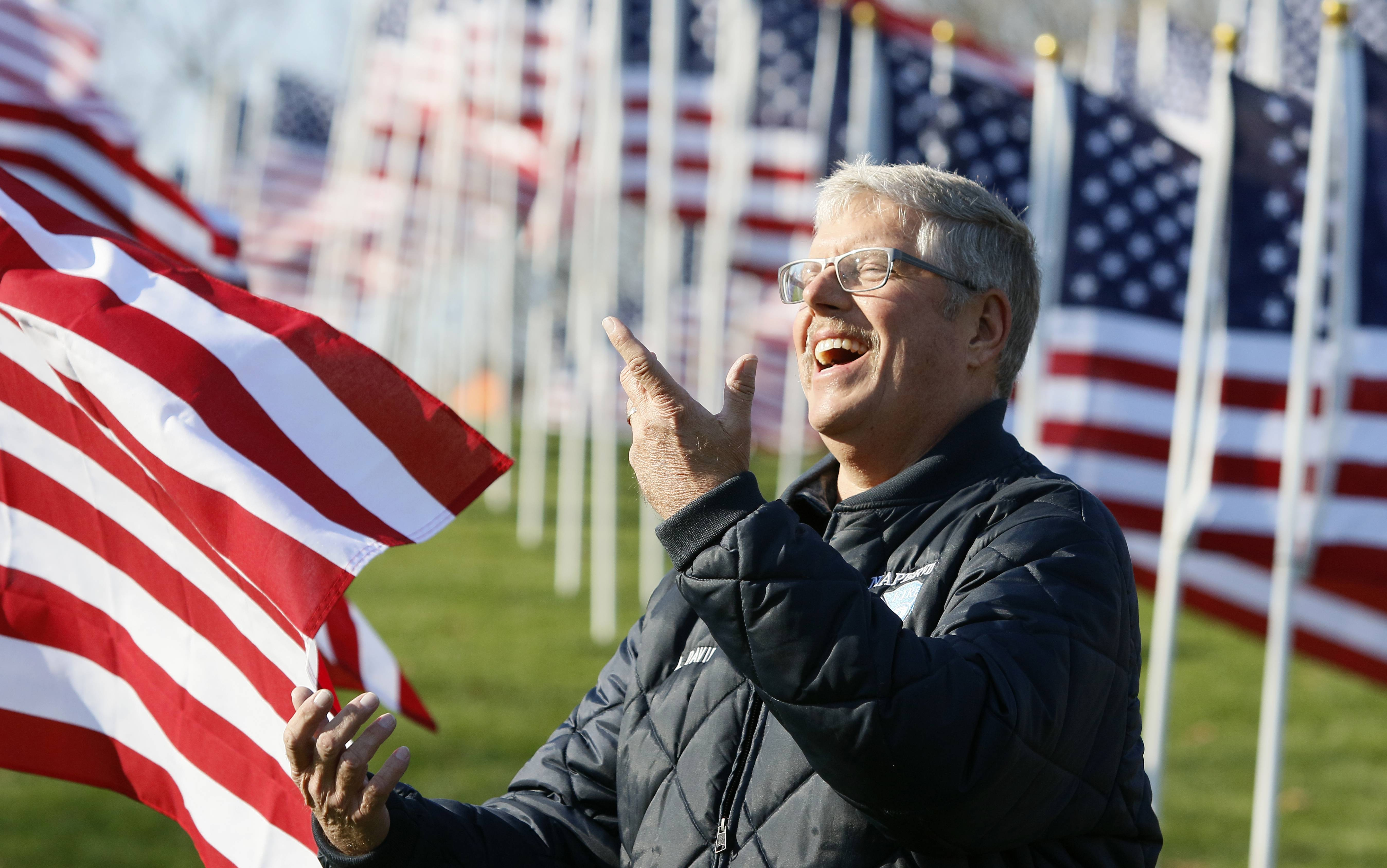Naperville firefighter Kent David celebrates his last day on the job, after 24.5 years of service, at the Healing Field of Honor at Rotary Hill. David and fellow firefighters attended the Naperville Veterans Day ceremony.