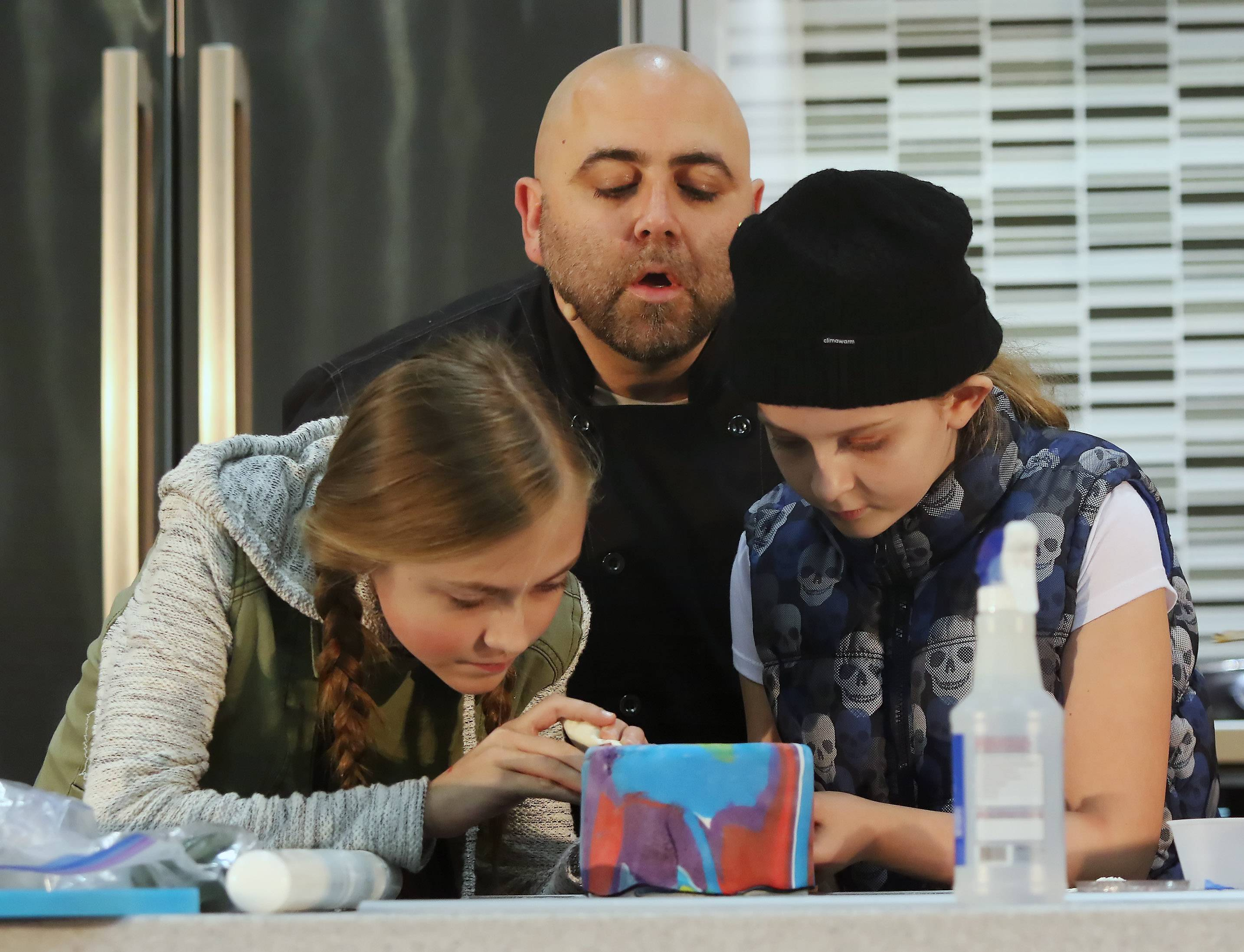 "Television chef Duff Goldman, known as the ""Ace of Cakes,"" watches as his young assistants, Amber Ogrodnik, 12, of Chicago, left, and Makenzie Blake, 10, of Huntley decorate a cake during America's Baking and Sweets Show Sunday at the Schaumburg Convention Center at the Renaissance Hotel. Goldman is recognized for his hit show ""Ace of Cakes"" that ran on the Food Network for ten seasons."