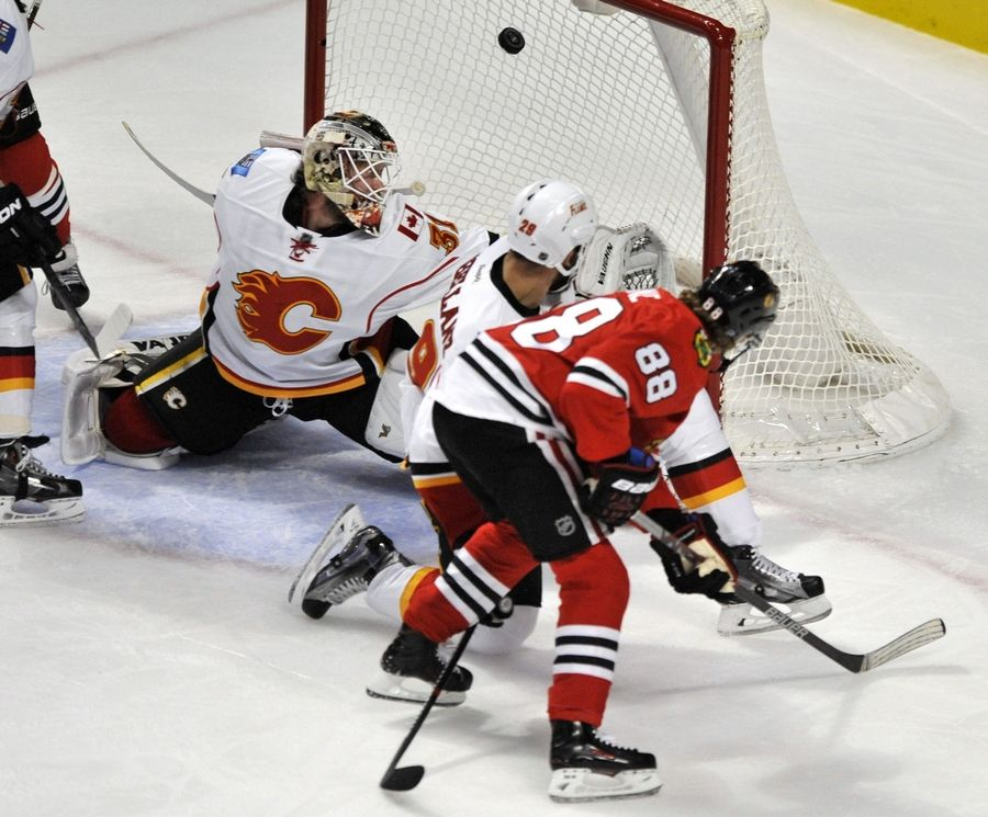 The Chicago Blackhawks' Patrick Kane slips the puck past Calgary Flames goalie Karri Ramo during the second period of Sunday's game at the United Center.